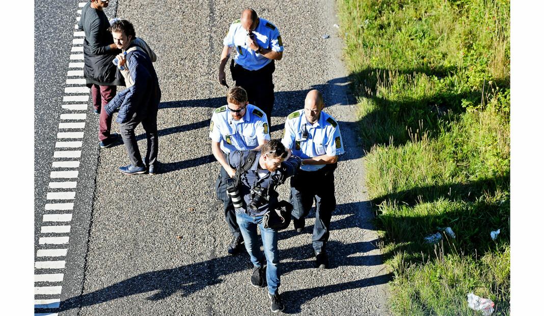 Politikens fotograf Martin Lehmann føres bort av politiet da han nektet å etterkomme deres ordre om å forlate motorveien, der han dokumenterte flyktninger. Foto:Ernst van Nord / Ritzau