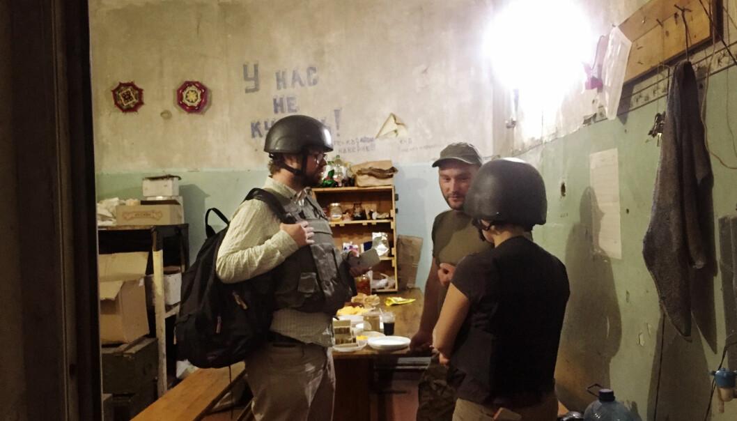 Frilansjournalist Per Christian Selmer-Anderssen i samtale med en ukrainsk troppsjef for Brigade 93 ved frontlinjen i nærheten av landsbyen Krymske i Øst-Ukraina, ikke langt unna de russiskstøttede opprørerer-skarpskyttere. Han er iført skuddsikker vest og hjelm, da det ofte kommer både granater og tyngre skyts inn mot possisjonen til det Ukrainske militæret. Foto: Kyrre Lien