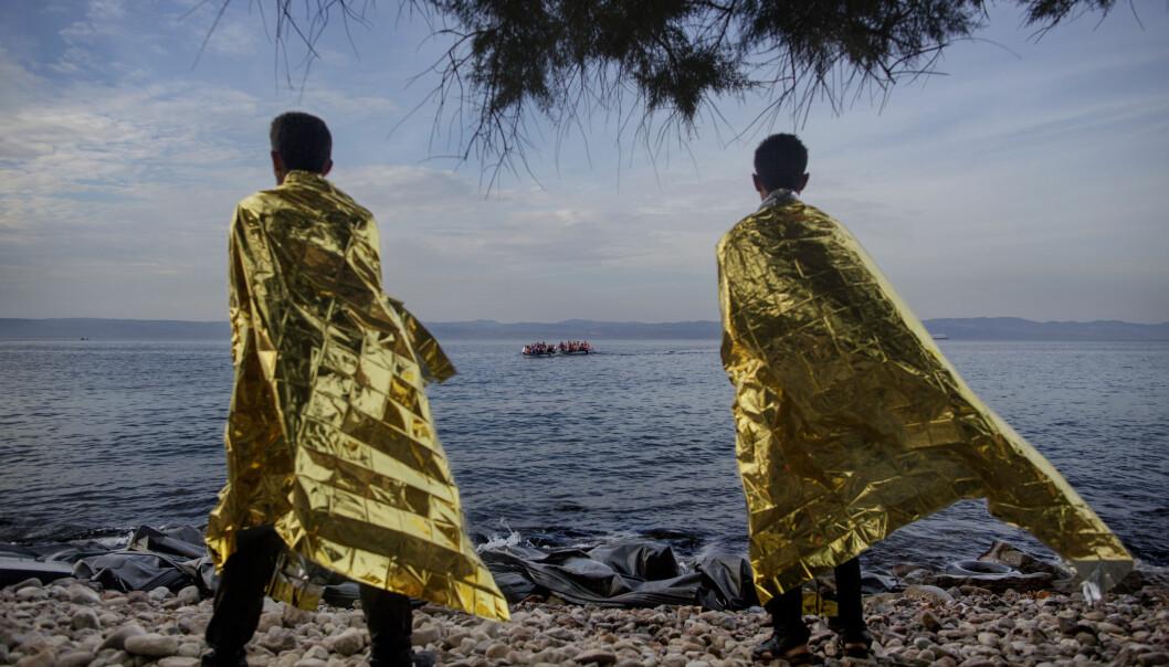 To syriske flyktninger står på stranden på Lesbos og ser ut på Middelhavet hvor nye flyktninger er på vei mot håpet. Foto: Espen Ramussen/VG.