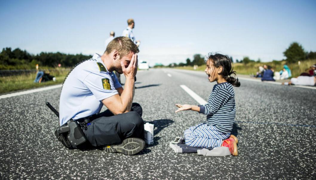 ÅRETS BILDE: Politimannen som leker med flyktningjenta på motorveien i Danmark, stakk av med prisen for årets nyhetsbilde. Foto: Michael Drost-Hansen/Jyllands-Posten.
