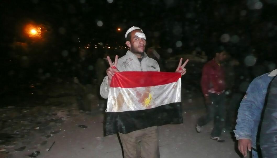 Tahrir-plassen. Natt til 3. februar. Regimekritiker viser seierstegn og et blodig flagg etter å ha slåss mot Mubarak-tilhengere. Foto: aljazeeraenglish (Flick.com)