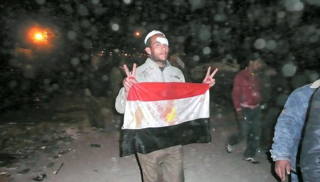 Tahrir Square. Natt til 3. februar. Regimekritiker viser seierstegn og et blodig flagg etter å ha slåss mot Mubarak-tilhengere. Foto: aljazeeraenglish (Flick.com)
