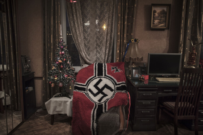 Et knyttet teppe med hakekors ligger halvferdig over en stol hjemme hos 28 år gamle «Shadow» utenfor Moskva, Russland. Hun har selv laget teppet. Hun og forloveden «John Wagner» er med i den nasjonalsosialistiske og nazistiske gruppen KNS – Komitee for Nation and Freedom. Foto: Espen Rasmussen