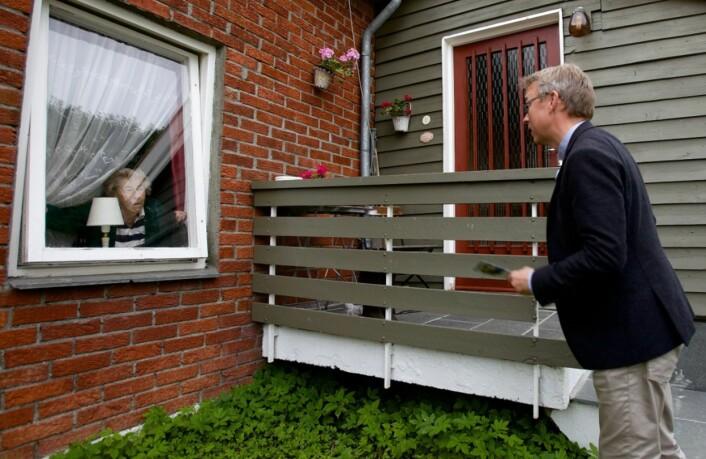 Hedvig Synnøve Svendsen kommer til vinduet når Morten Skandfer ringer på. Stortingskandidaten ber om å få legge flygebladet på trappa. Det er greit. Foto: Ola Solvang/Nordlys
