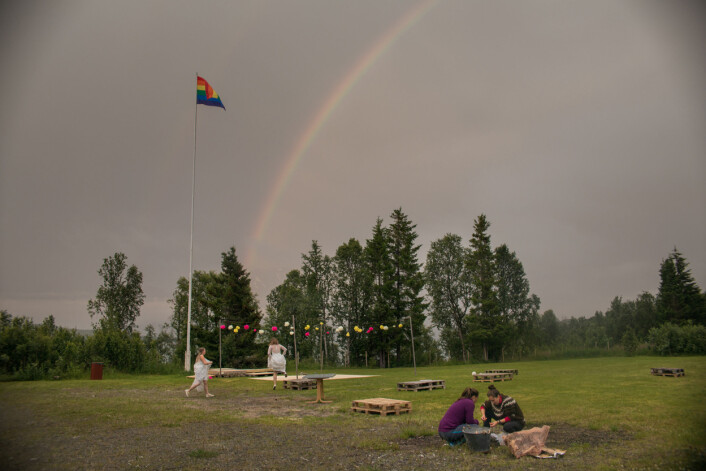 Regnbueflagget vaier under en dobbel regnbue i Lyngen. Brudeparet spretter ørville rundt.Foto:Annemor Larsen