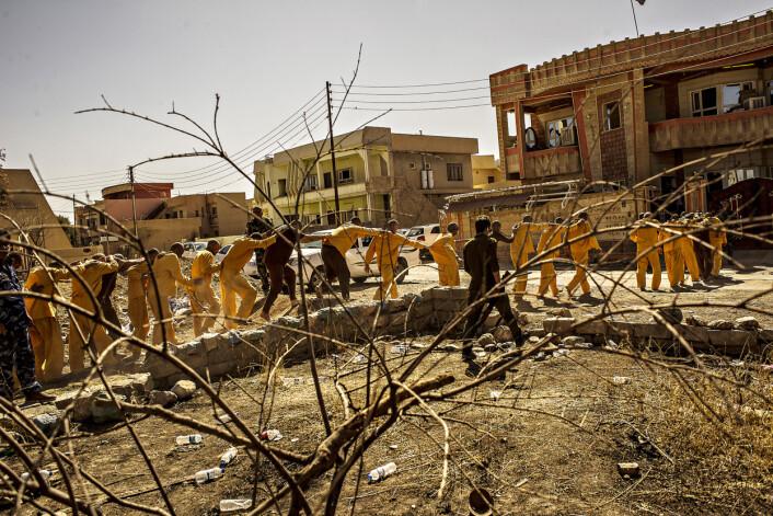 En gruppe mistenkte IS-medlemmer føres fra fangetransporten til rettsbygningen i den kristne byen Qaraqosh – byen som IS noen måneder tidligere la i ruiner. De skyldige risikerer å møte galgen i Bagdad.Foto:André Liohn