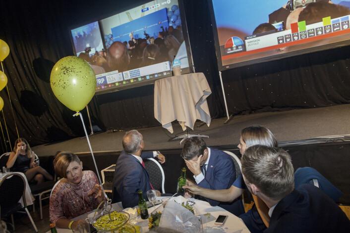 KrF-leder Knut Arild Hareide går rundt til partimedlemmer under valgvaken på valgnatten. Deler av KrFs ledelse ser valgsdagsmålingen komme opp på storskjerm. Selv om det ble borgerlig seier, gjorde KrF sitt dårligste valg etter krigen. Foto:Espen Rasmussen