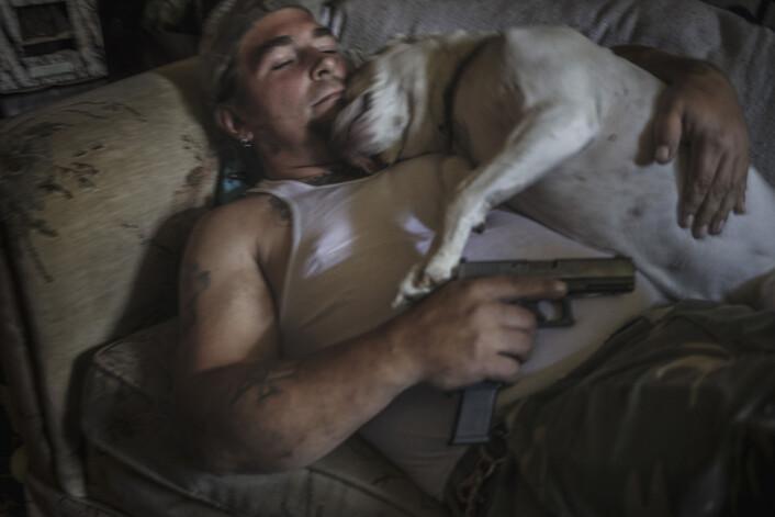 Lederen av militsgruppen My Brothers Threepers, Danny Bollinger (43), på sofaen i stua i Maryland. Han har ere titalls våpen spredd rundt i huset og øver hver dag i hagen. Foto:Espen Rasmussen