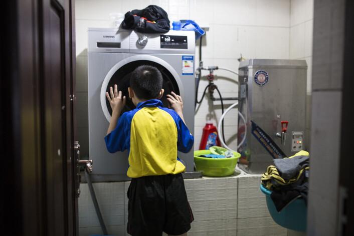 Huang og de andre barna har selv ansvaret for renholdet. Huang venter på tur for å bruke vaskemaskinen. Foto:Javier Auris
