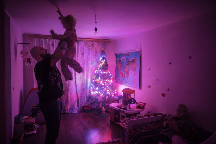 Evgenij Stojka leker med sin datter før hun skal legge seg for kvelden i leiligheten deres i utkanten av Kiev, Ukraina. Både han og konen er ny-nazister. Foto:Espen Rasmussen