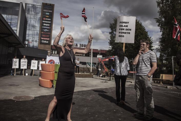 Anna Bråten vifter med norske flagg og roper mot flere hundre motdemonstranter. De har møtt fram for å vise sin avsky mot henne og organisasjonen SIAN – Stopp Islamifiseringen av Norge - på Furuset i Oslo. Foto:Espen Rasmussen