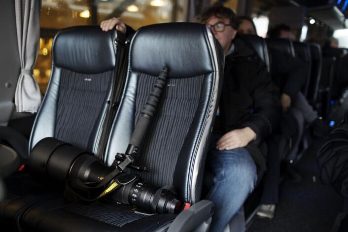 En Nikon telelinse har fått kongeplass på første rad på bussturen til flyplassen. Foto: Andrea Gjestvang