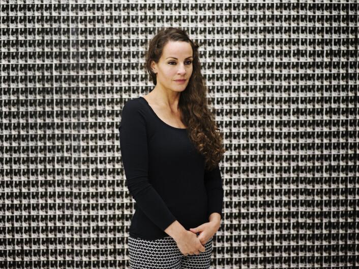 Linda Bournane Engelberth foran galleriveggen på NoPlace, som er tapetisert med fotografier av moren og henne selv. Foto: Andrea Gjestvang