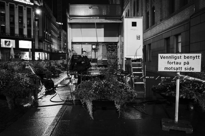 Utenfor Stortinget på Karl Johan står en ensom kameramann fra NRK i ly for regnet ved traileren.