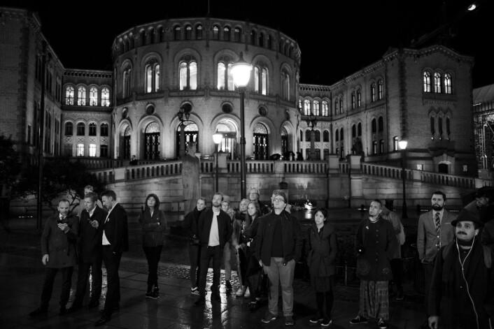 Utenfor Stortinget står folk i regnet og ser på NRKs storskjerm med partilederdebatten.