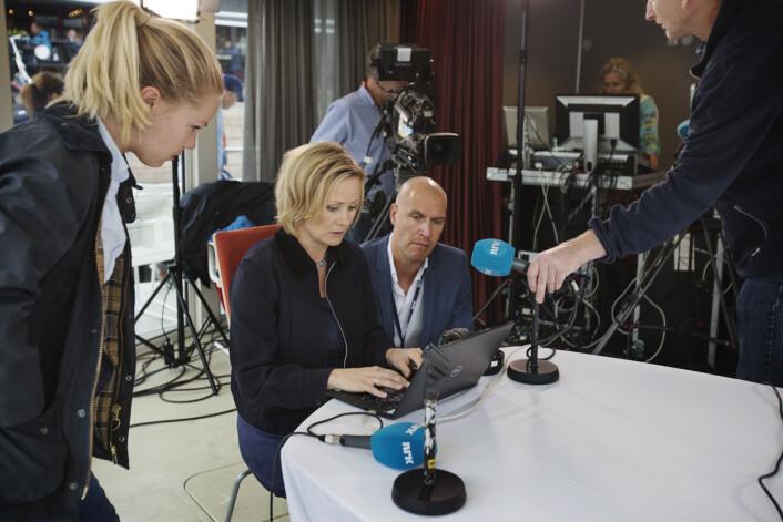 """Reporter Sophie Lorch-Falch gir sin overlevering til programleder Sigrid Sollund og vaktsjef Fredrik Lauritzen rett før dagens sending. Se <a href=""""https://journalisten.no/sites/default/files/_28a6777.jpg"""">større bilde her</a>."""