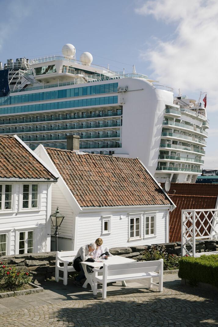 To turister kikker på et kart i gamle Stavanger. Bak idyllen ruver skip med tusenvis av passasjerer.