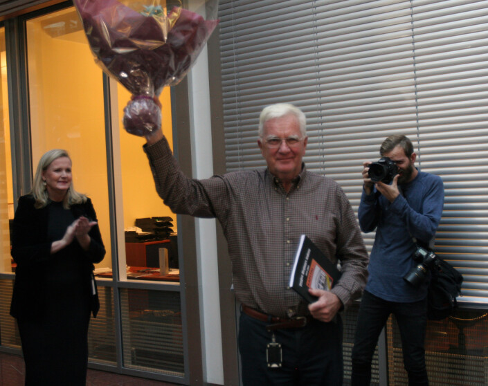 Hegnar mottok boken over alle ledernes titler fra Kapitals redaktør Vibeke Holth, samt blomster fra de ansatte. Foto: Glenn Slydal Johansen