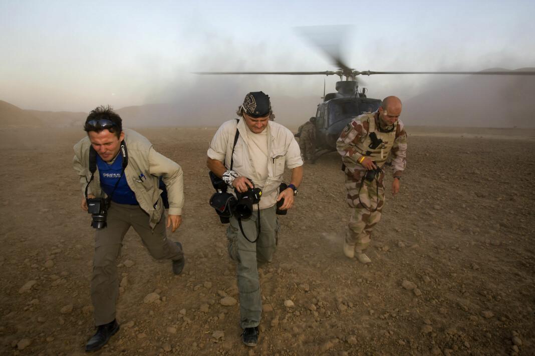 Harald Henden (midten) løper vekk under en øvelse med to av forsvarets Bell helikoptere, sammen med Aftenposten-journalist Tor Arne Andreassen og medieoffiser Bengt Eidem, i Nord Afghanistan i 2008. Foto: Heiko Junge / NTB SCANPIX