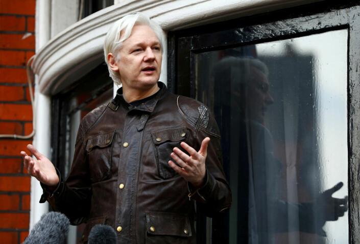 Julian Assange snakker til journalister fra vinduet i ambassaden.