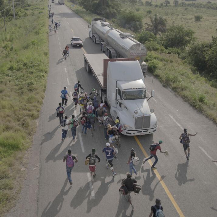 Folk løper til en lastebil som har stoppet for å gi dem skyss, utenfor Tapanatepec, Mexico, 30. oktober 2018. Noen sjåfører tok betalt for å gi reisende skyss et stykke på veien, men de fleste tilbød gratis tjenester for å støtte flyktningene. Foto: Pieter Ten Hoopen, Agence Vu/Civilian Act