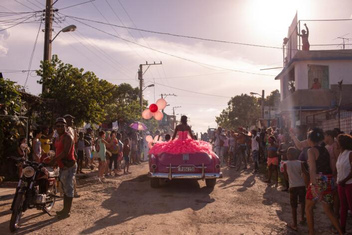 Pura kjører rundt i nabolaget i en rosa bil fra 50-tallet, mens lokalsamfunnet samler seg for å feire hennes 15-årsdag i Havana, Cuba. Foto: Diana Markosian / Magnum Photos