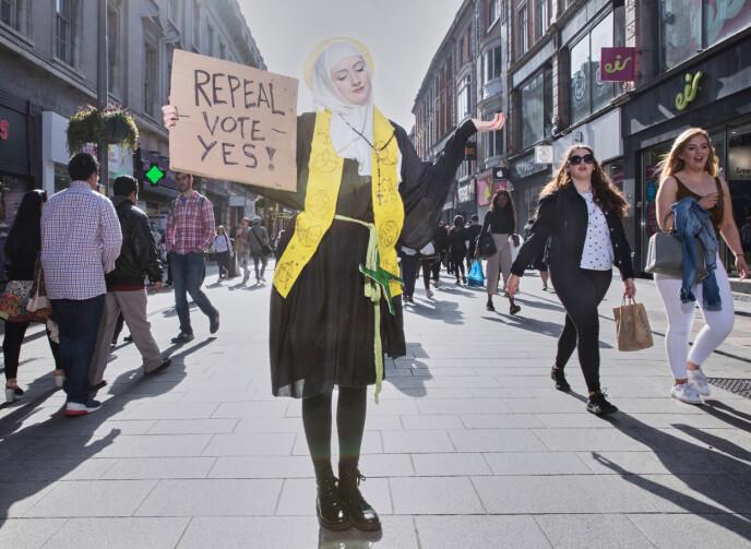 Amort Scott, er kledd som St. Brigid, Irlands kvinnelige helgen, poserer for et fotografi i Dublins største handlegate, den 21. april. Foto: Olivia Harris