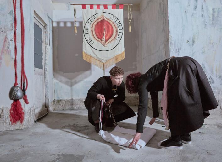 Kvinner bretter et tøystykke foran en banner med teksten «Our Toil Doth Sweeten Others», skapt av artisten Alice Maher, på <i>Eva International Art Festival i Limerick i</i> Irland. Kampanjer for abort bruker kunst for å ta opp emner som tidligere var vurdert som ikke-temaer i et konservativt samfunn. Foto: Olivia Harris