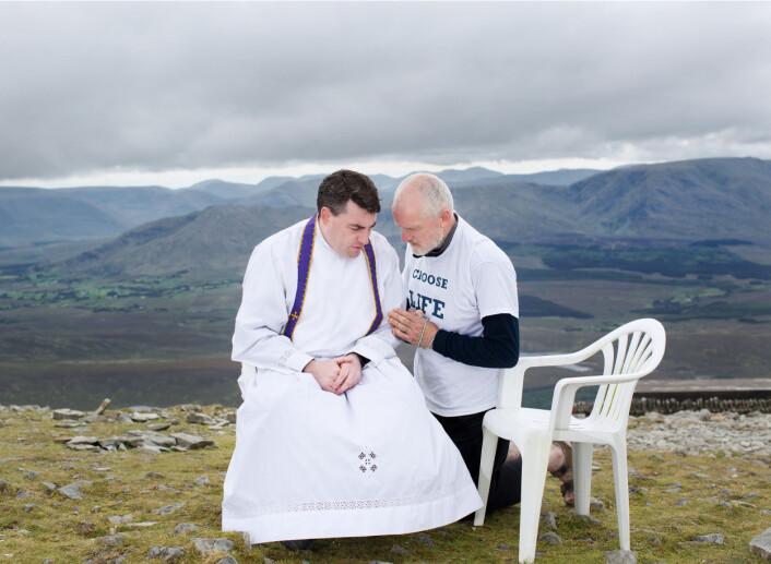 Aidan ber med en prest etter skriftemål, på toppen av det hellige fjellet Croagh Patrick, i County Mayo i Irland. Mange pilegrimer kommer til dette fjellet, inkludert en pro-livsgruppe for menn. Foto: Olivia Harris