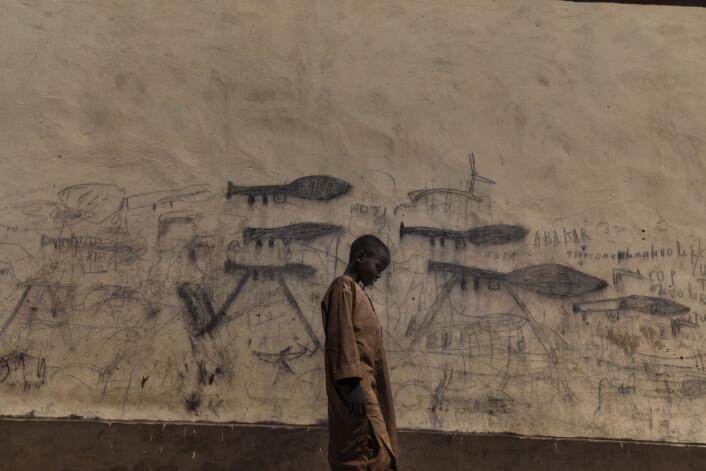 En foreldreløs gutt går forbi en vegg med tegninger av rakettdrevne granatkastere, i Bol, Tsjad. Mange foreldreløse barn, inkludert nigerianske flyktninger, bor på koranskoler og blir sendt ut for å tigge deler av dagen. Foto: Marco Gualazzini / Contrasto