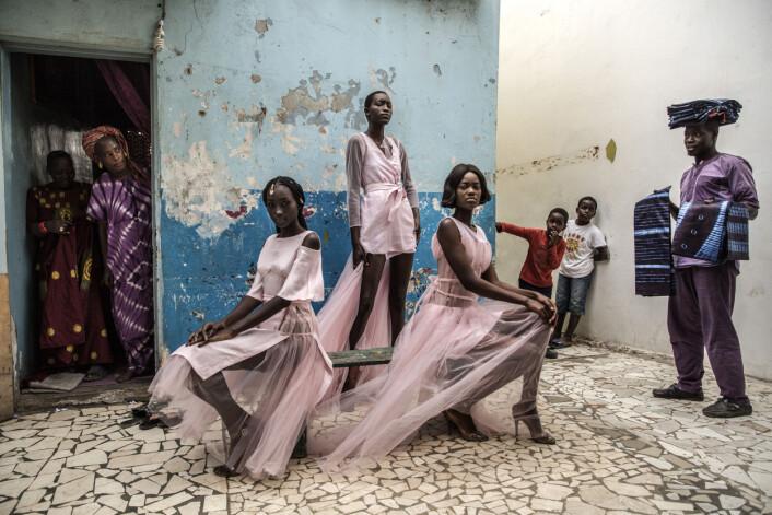 Diarra Ndiaye, Ndeye Fatou Mbaye og Mariza Sakho står som modeller for antrekk av designer Adama Paris, i Medina-området i Senegals hovedstad, Dakar, mens nysgjerrige innbyggere ser på. Foto: Finbarr O'Reilly