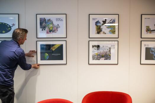 Odd Klaudiussen retter litt på et par av tegningene som henger i iTromsø-redaksjonen.