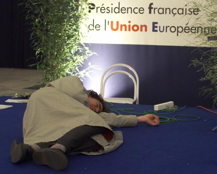 En trøtt journalist sover på gulvet i pressesenteret under et maratonmøte i EU i Nice, 11. desember 2000. Foto: Eric Gaillard, Reuters
