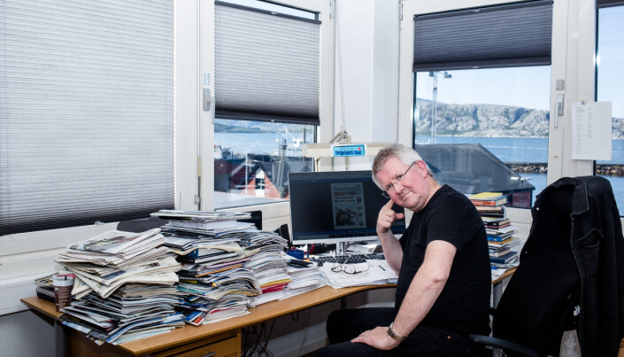 Morten Hofstad har stabler med aviser på pulten som har utsikt til fjorden i Sandnessjøen. Foto: Eskil Wie Furunes