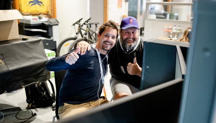 André Askeland og Alf Vidar Snæland viser en tommel opp til fotografen på pressesenteret på Norway Cup. De måtte flytte hit etter kablene for internett ble kuttet til sendekontrollen. Foto: Eskil Wie Furunes