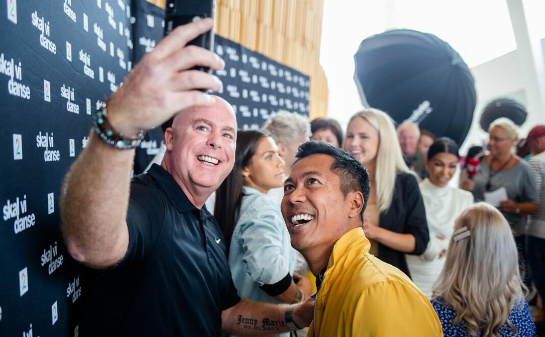 Tidligere ishockeyspiller Jan Tore Kjær og NRK-programleder Christian Strand tar en selfie sammen under presentasjonen av årets Skal vi danse-deltakere. Foto: Eskil Wie Furunes