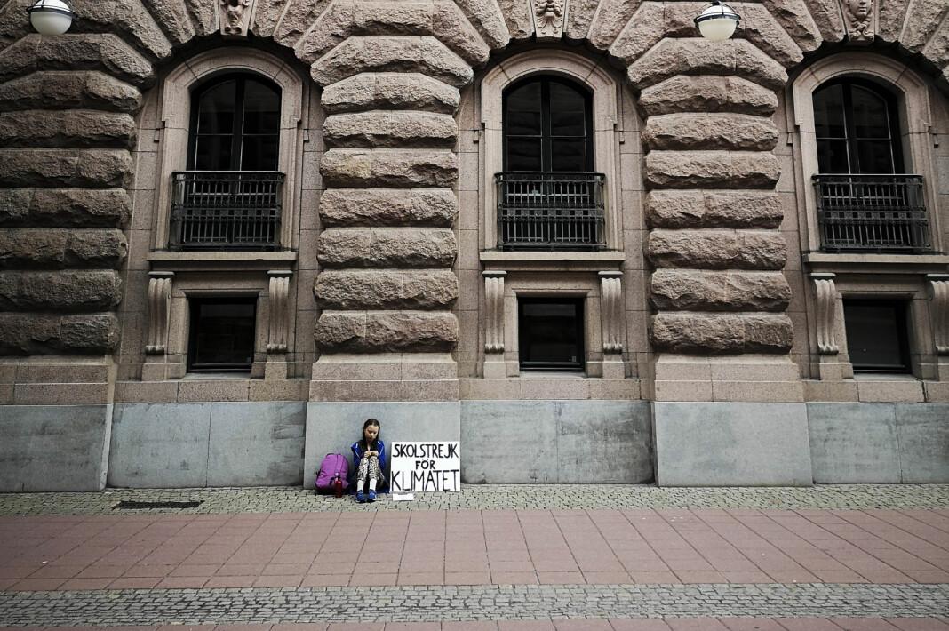 Greta Thunberg satt helt alene utenfor Riksdagen en fredag i fjor, i sin stille protest for klimaet. Dette mobilbildet tatt av Adam Johansson ble senere spredt i sosiale medier. Foto: Adam Karls Johansson / TT / NTB scanpix