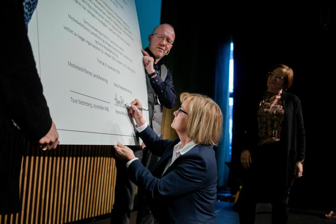 Styreleder Hanna Relling Berg i Norsk Redaktørforening signerer den nye Redaktørplakaten, mens generalsekretær Arne Jensen holder plakaten. I bakgrunnen ser vi styreleder Tove Nedreberg i MBL som venter på sin tur til å signere. Foto: Eskil Wie Furunes