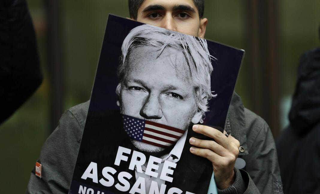 En av Julian Assanges støttespillere med en plakat av den nå 48 år gamle australieren. Foto: Kirsty Wigglesworth / AP / NTB scanpix
