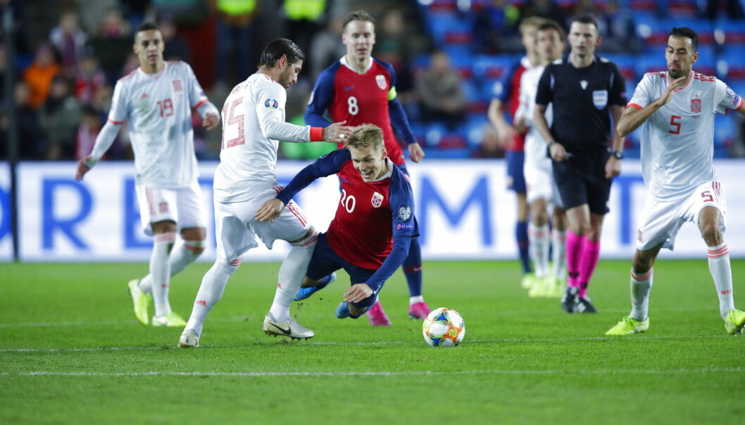 Martin Ødegaard felles av Spanias Sergio Ramos i en landskamp. Lørdag møtes de trolig i seriekamp i La Liga. Foto: Stian Lysberg Solum / NTB scanpix