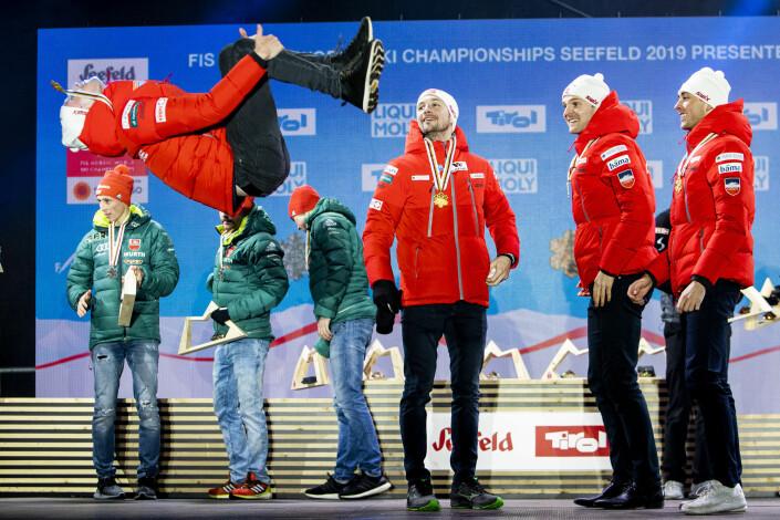 Espen Bjørnstad tar en salto og markerer gullet i lagkonkurransen kombinert i Seefeld-VM. Lagkameratene Jan Schmid, Jarl Magnus Riiber og Jørgen Graabak følger imponert med. Foto: Tore Meek / NTB scanpix