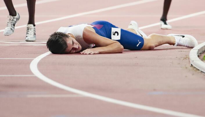 Jakob Ingebrigtsen blir liggende utslått på tartandekket etter femteplassen på 5000-meteren under VM i Doha. Foto: Lise Åserud / NTB scanpix