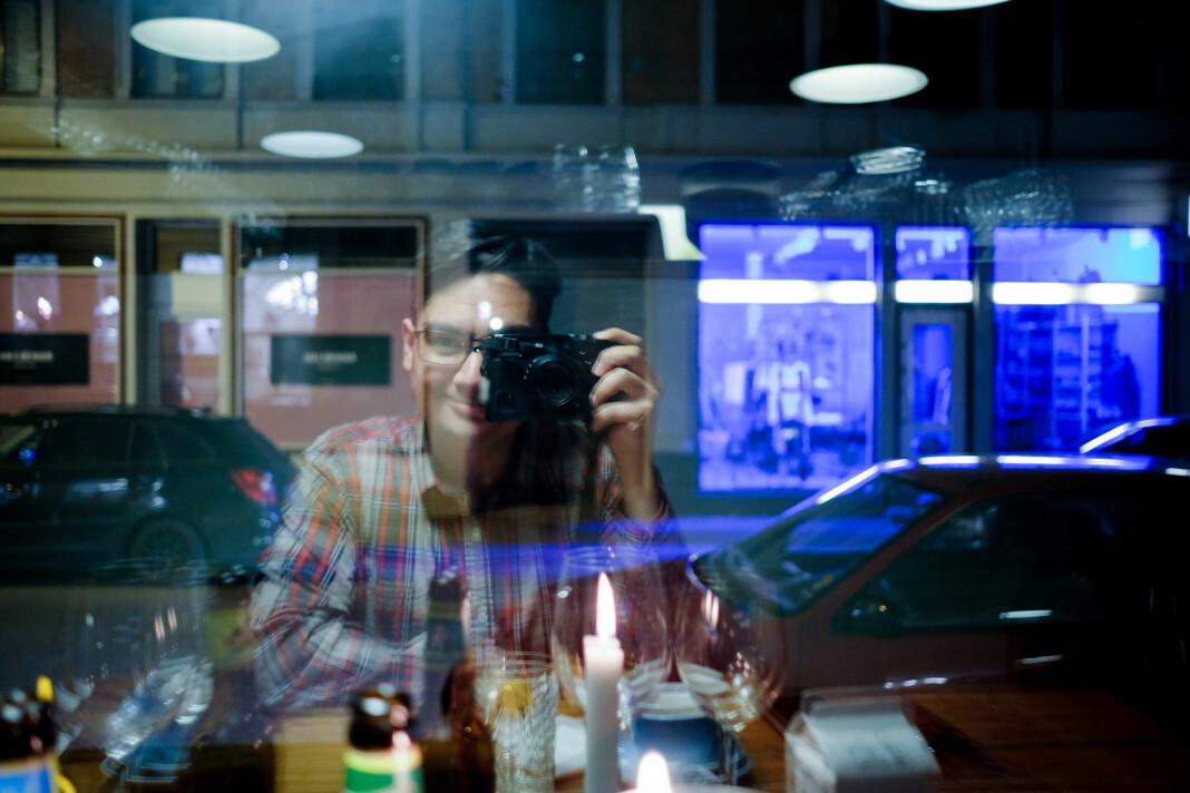 Frilansfotograf Joakim S. Enger, her et selvportrett i et restaurantvindu i Aarhus i Danmark.