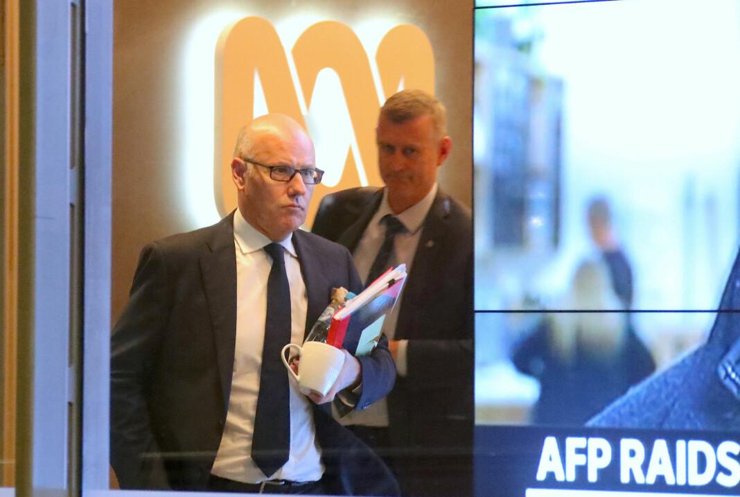 John Lyons, ansvarlig redaktør i ABC News i Australia, går ut av ABCs lokaler, fulgt av en politibetjent.