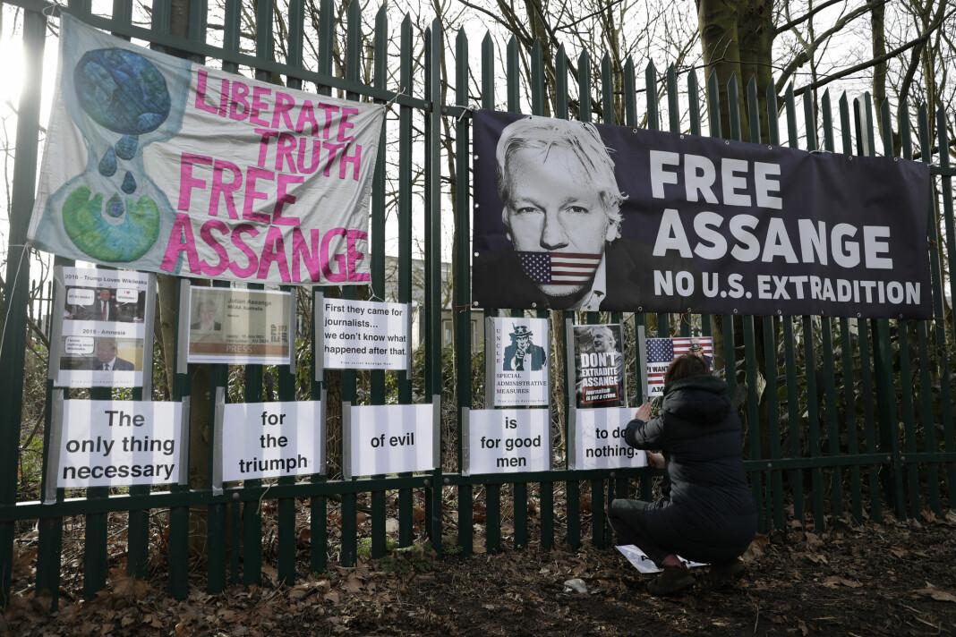 En av Julian Assanges støttespillere henger opp protestplakater mot at WikiLeaks-grunnleggeren utleveres til USA.