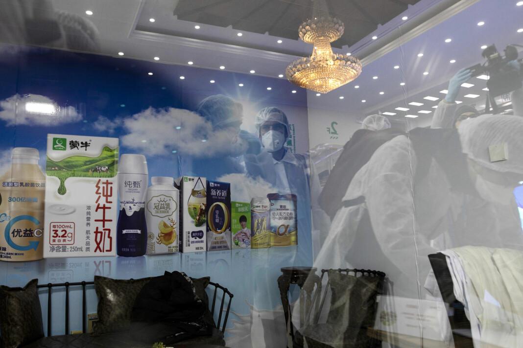 KINA: Utenlandske journalister har på seg fullt beskyttelsesutstyr da de besøker meieri-fabrikken Mengniu i Beijing i februar 2020. Her ser vi journalistene reflektert i en glassflate på fabrikken.