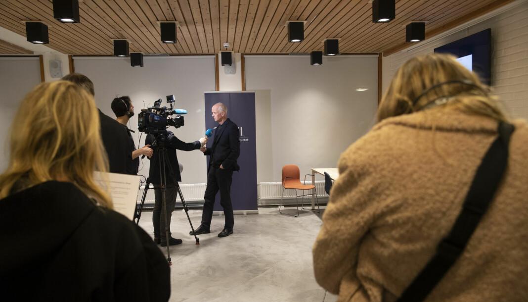 Områdedirektør Geir Bukholm i Folkehelseinstituttet blir intervjuet, mens andre står i kø.