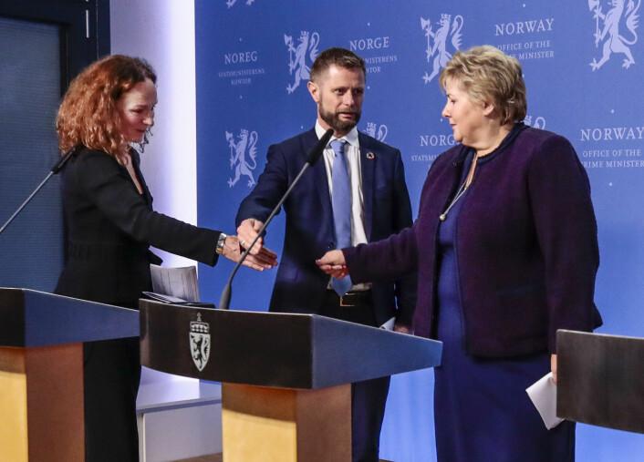 Pressekonferanse 12. mars: Helseminister Bent Høie avverger at direktør for Folkehelseinstituttet Camilla Stoltenberg (t.v) og statsminister Erna Solberg håndhilser.