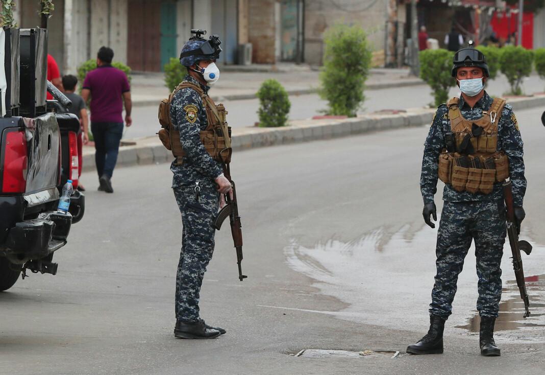 Irakiske sikkerhetsstyrker med munnbind patruljerer i Bagdad, der det er innført portforbud.