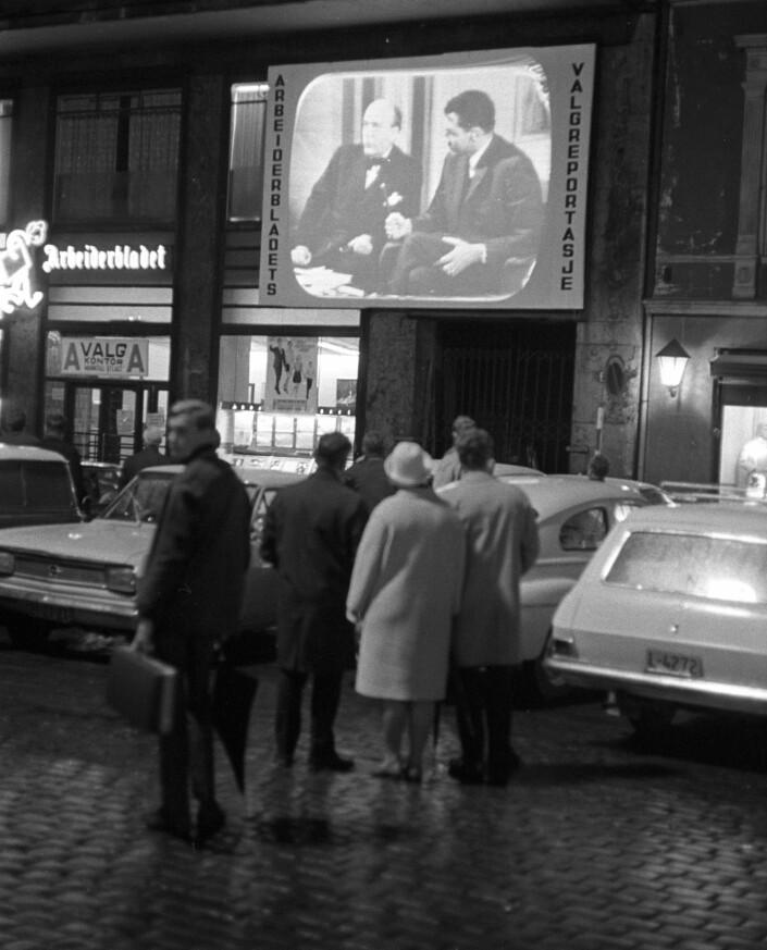 ETT FOLK: Her ser vi et bilde tatt av Dagbladets fotograf, Odd Wentzel. Året er 1967 og Arbeiderbladet hadde satt opp en stor fjernsynsskjerm på Youngstorget for å vise bilder fra kommunevalget. Bildet har selvsagt ingenting med noen av sakene våre å gjøre, det skulle tatt seg ut, men bildet er fint da. I skumle pressetider som dette.